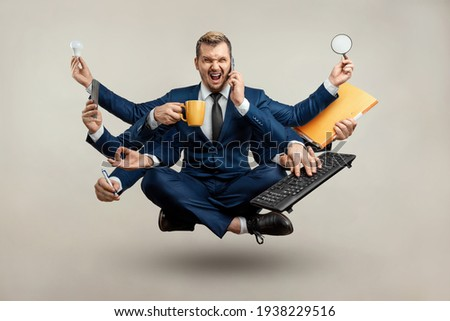 Businessman with many hands in a suit. Works simultaneously with several objects, a mug, a magnifying glass, papers, a contract, a telephone. Multitasking, efficient business worker concept