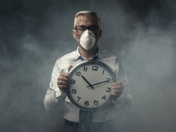 Businessman with mask holding a clock and polluted air, doomsday warning concept
