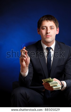 Businessman  with money over blue background