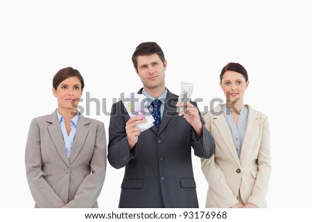 Businessman with money standing between employees against a white background