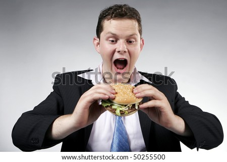 Businessman with mouth wide opened, ready to eat a burger