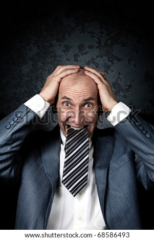 Businessman with Necktie in his mouth holding his head with hands on grunge background
