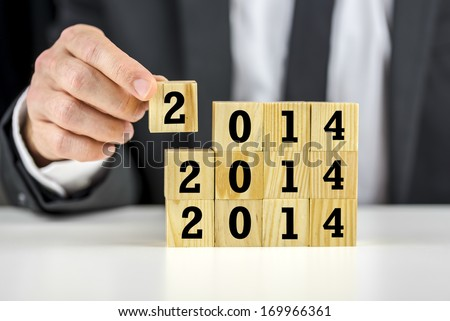 Businessman with 2014 New Year building blocks carefully stacking them on top of each other depicting business planning, strategy and development in the forthcoming year