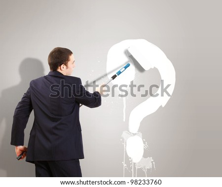 Businessman with paint brash and picture of question mark on the wall