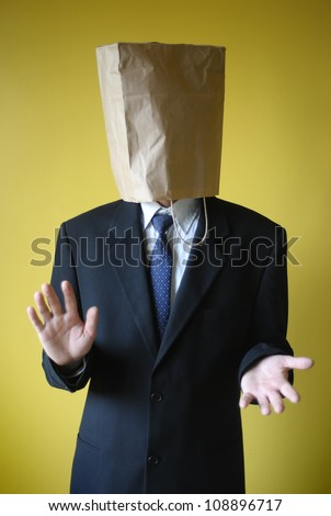 Businessman with paper bag on a head - stock photo