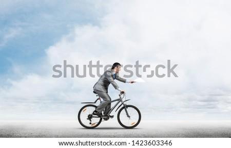 Businessman with paper documents in hand on bike. Deadline for paperwork. Corporate employee in grey business suit riding bicycle on background of skyscape. Accounting and financial statements #1423603346