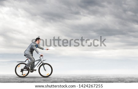 Businessman with paper documents in hand on bike. Deadline for paperwork. Corporate employee in grey business suit riding bicycle on background of skyscape. Accounting and financial statements #1424267255