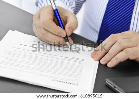 Businessman with pen  signing a contract #610895015