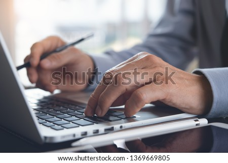 Businessman with pencil in hand working on laptop computer keyboard in modern office, online job concept. Man typing on laptop, searching internet with digital tablet on office desk, online working