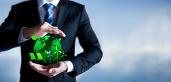 Businessman with protective gesture a green globe icon. eco-friendly business. Business and environmental concepts with copy space