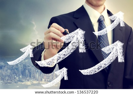 Businessman with rising arrows showing success with big city backdrop