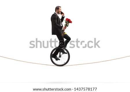Businessman with roses talking on a phone and riding a unicycle on a rope isolated on white background  #1437578177
