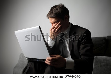 businessman with sad expression and a laptop