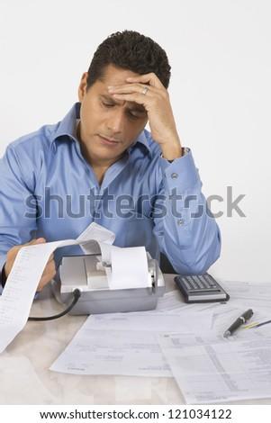 Businessman with severe headache calculating finance