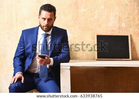 businessman with smartphone in business office, young man with mobile phone and blackboard on table
