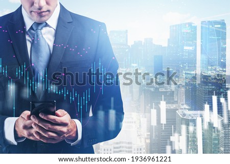 Businessman with smartphone in hands analysing stock market changes, double exposure of city buildings, blue candlesticks. Concept of online trading
