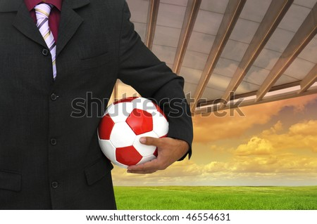 Businessman with soccer ball in a stadium like background