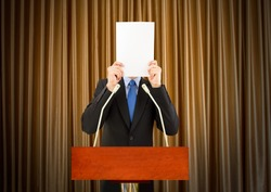 businessman with stage fright covering his face with a sheet of paper to a podium to speak for being embarrassing