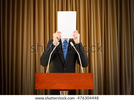businessman with stage fright covering his face with a sheet of paper to a podium to speak for being embarrassing Stock photo ©