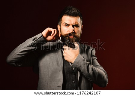 Businessman with strict face on dark red background. Macho in formal suit holds and cuts beard and moustache. Man with long beard holds steel scissors. Business and barbershop service concept. #1176242107