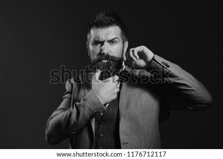 Businessman with strict face on dark red background. Macho in formal suit holds and cuts beard and moustache. Man with long beard holds steel scissors. Business and barbershop service concept. #1176712117