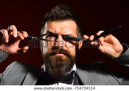 Businessman with strict face on dark red background. Man with beard holds razor and scissors in front of eyes. Macho in formal suit cuts and shaves beard and moustache. Business and barbershop concept #754734514