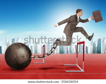 Businessman with suitcase and iron ballast jumping over treadmill barrier