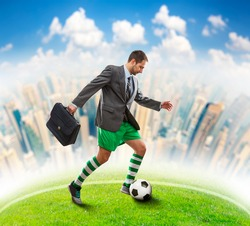 Businessman with suitcase in sportwear playing football in the town