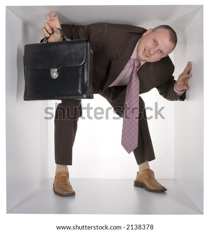 businessman with suitcase in the cramped white cube