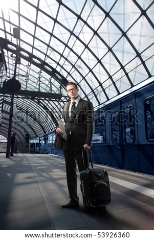 Businessman with suitcase standing on a platform of a train station