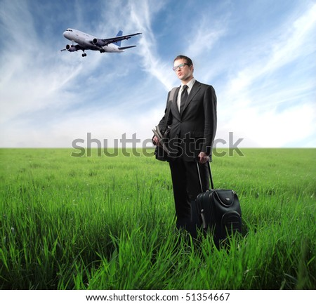 Businessman with suitcase standing on green meadow with airplane on the background