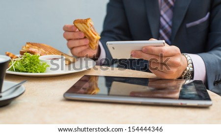 Businessman with tablet and smartphone during breakfast
