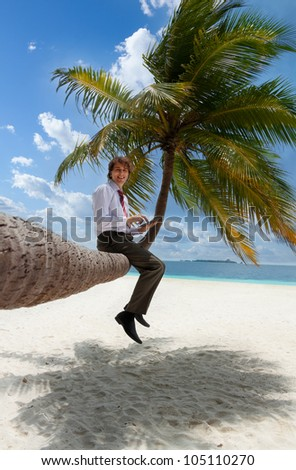 Businessman with tablet pc sitting on palm tree on the Maldivian beach and looking at camera smiling