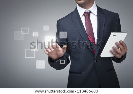 Businessman with tablet pushing on a touch screen interface