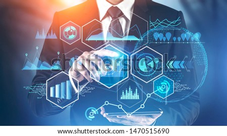 Businessman with tablet working with business infographics interface and digital graphs over blurred background. Concept of hi tech and stock market. Toned image double exposure #1470515690