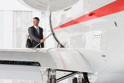 Businessman with the suitcase looking back while standing on the steps of a private jet