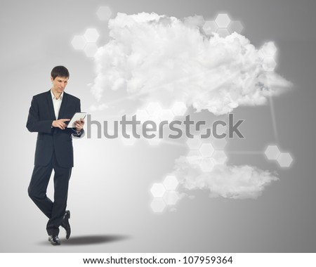 Businessman with touchscreen internet tablet and the clouds on grey background