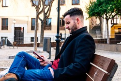 Businessman with trimmed beard sitting on a city bench. Using his mobile phone.