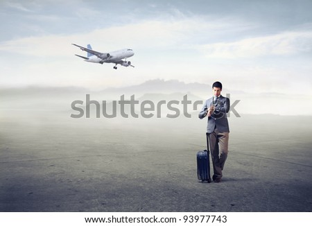 Businessman with trolley case looking at his watch with airplane in the background - stock photo