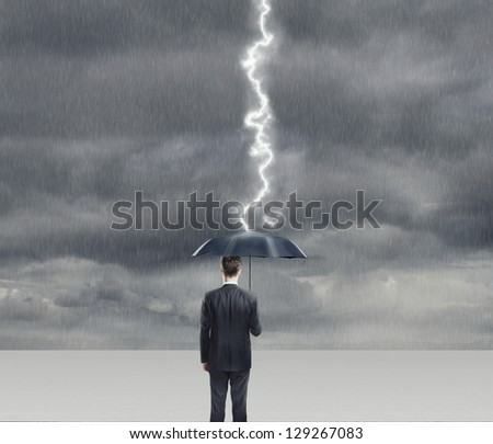 Businessman with umbrella in thunderstorm