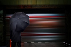 Businessman with umbrella on train station.