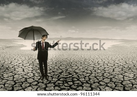 Businessman with umbrella standing on cracked earth waiting for the rain