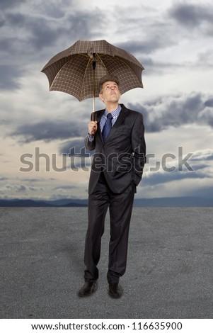 Businessman with umbrella under a stormy sky