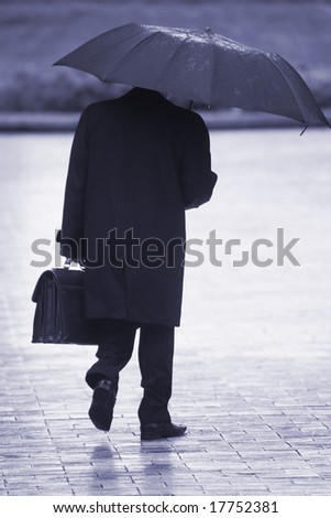 businessman with umbrella walking in the rain