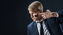 Businessman with war paint on his face. Risk management concept. young guy in suit with tie is preparing for a difficult job, make a war paint on the face