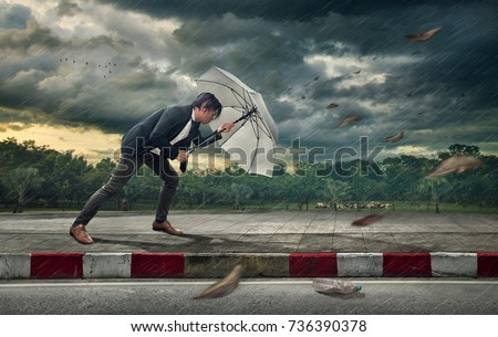 Businessman with white umbrella protecting himself from the storm.  Business heavy tasks and problems concept.