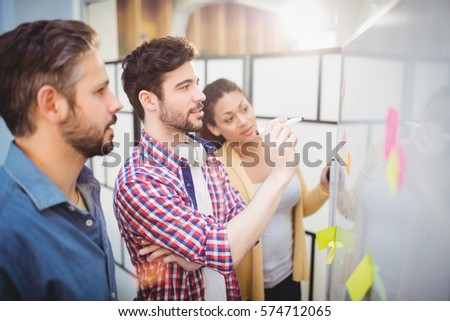 Businessman with young partners looking at whiteboard in creative office