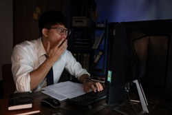 Businessman workaholic sit at the computer working late at night yawn tired and sleeping in the office,Hard work in the later time concept