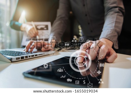 Businessman working as a team start meeting the new marketing project plan By business people using tablets and graph documents Calculate the amount of money for the project.