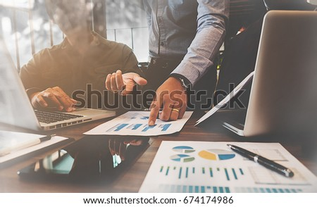 Businessman working at his coffee shop and using laptop discussing the charts and graphs showing the results of their successful teamwork.